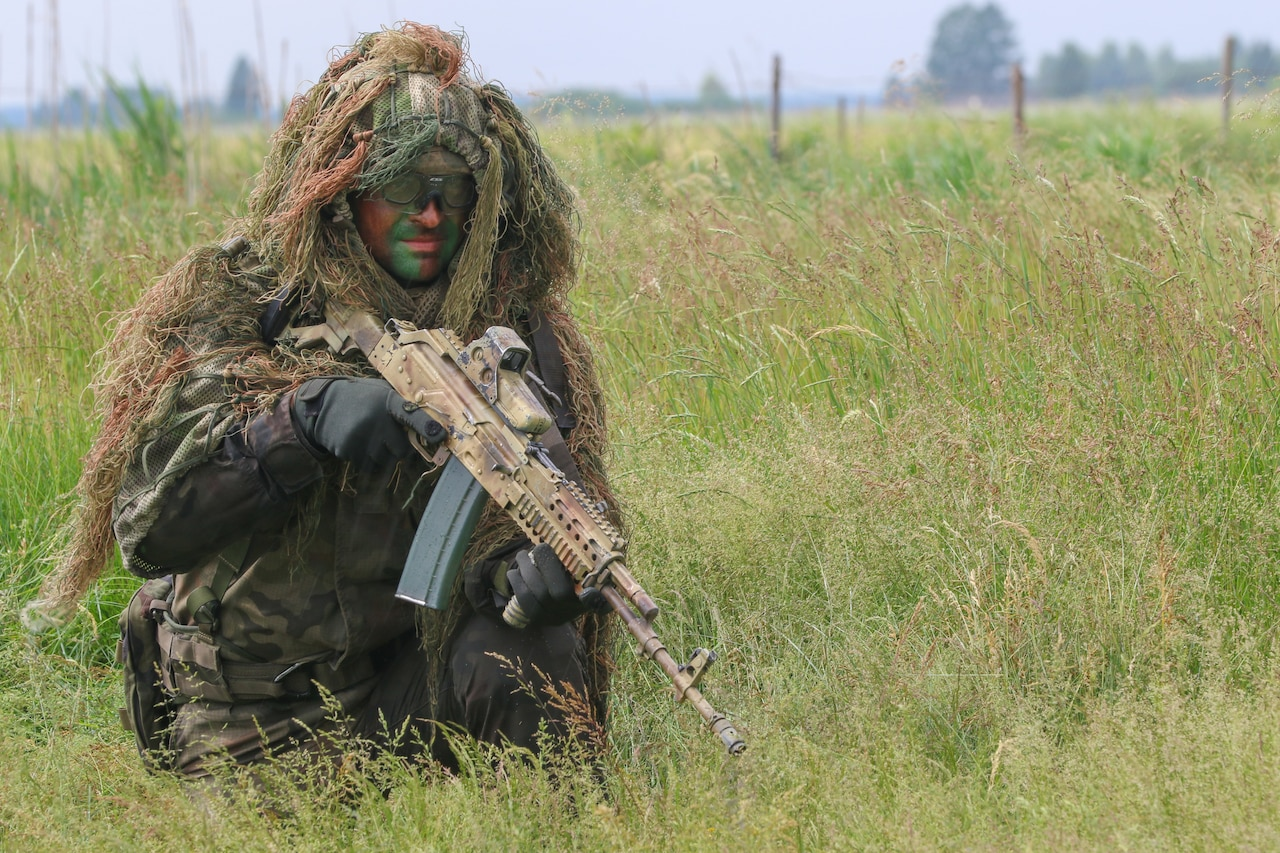 A service member kneels in a field. He holds a rifle, and wears a Guillie suit.