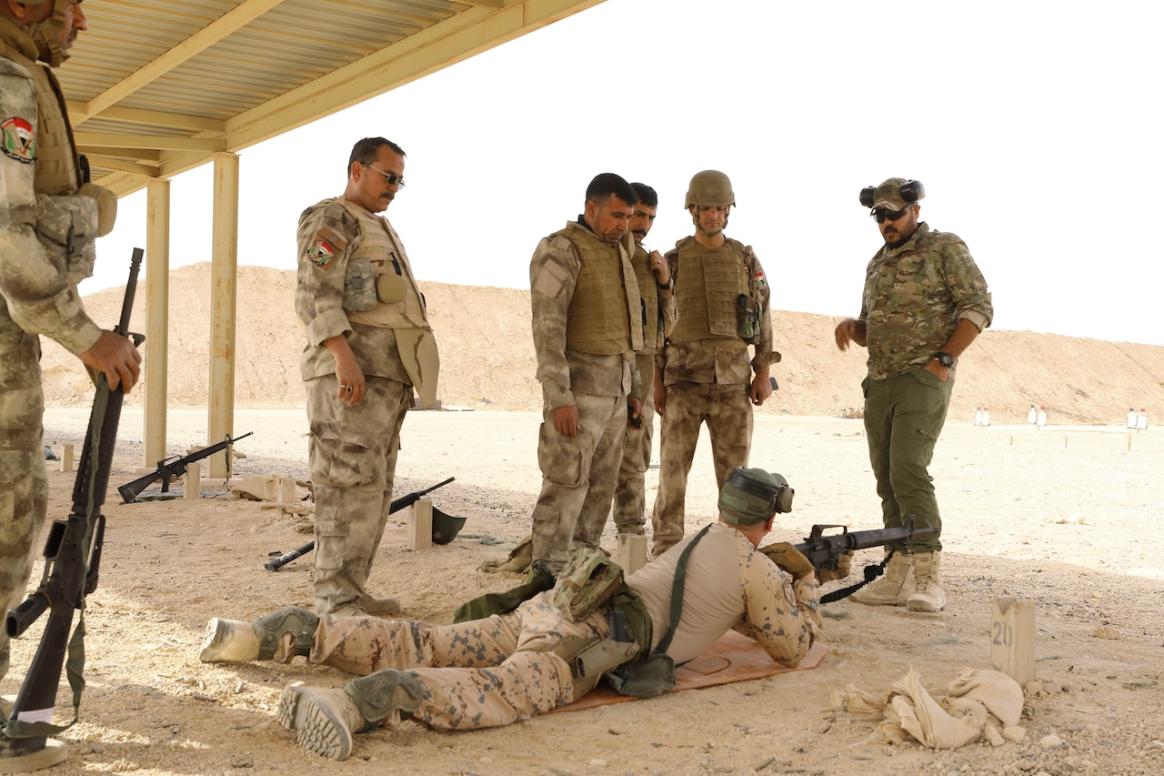 A service member lies on the ground with a rifle. Other service members are standing around him.
