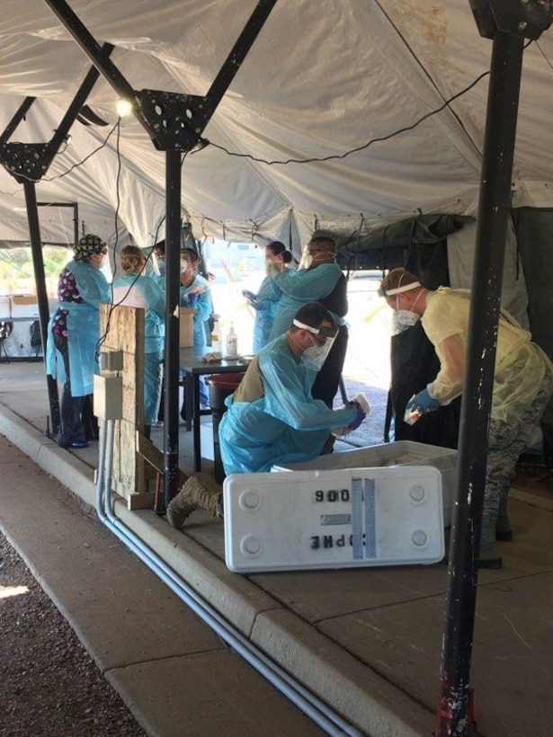 People in protective suits conducting COVID-19 testing