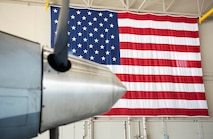 An American Flag sits in the back drop of an MQ-9 Reaper propeller.