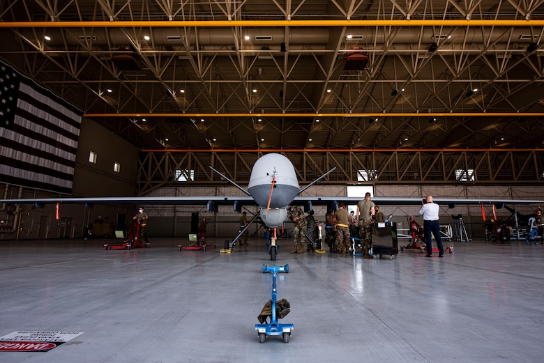MQ-9 Reaper sits in a hangar with 8 members preparing for routine maintenance.