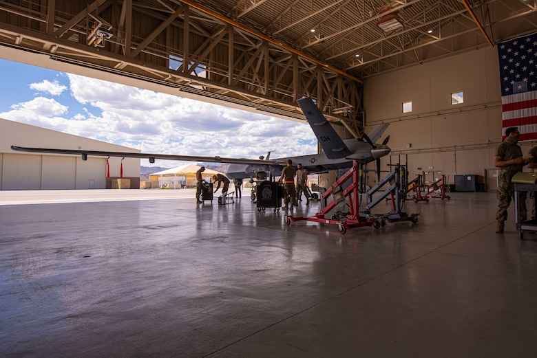 An MQ-9 Reaper sits in a hangar with a crew of 5 members as they prepare for routine maintenance.
