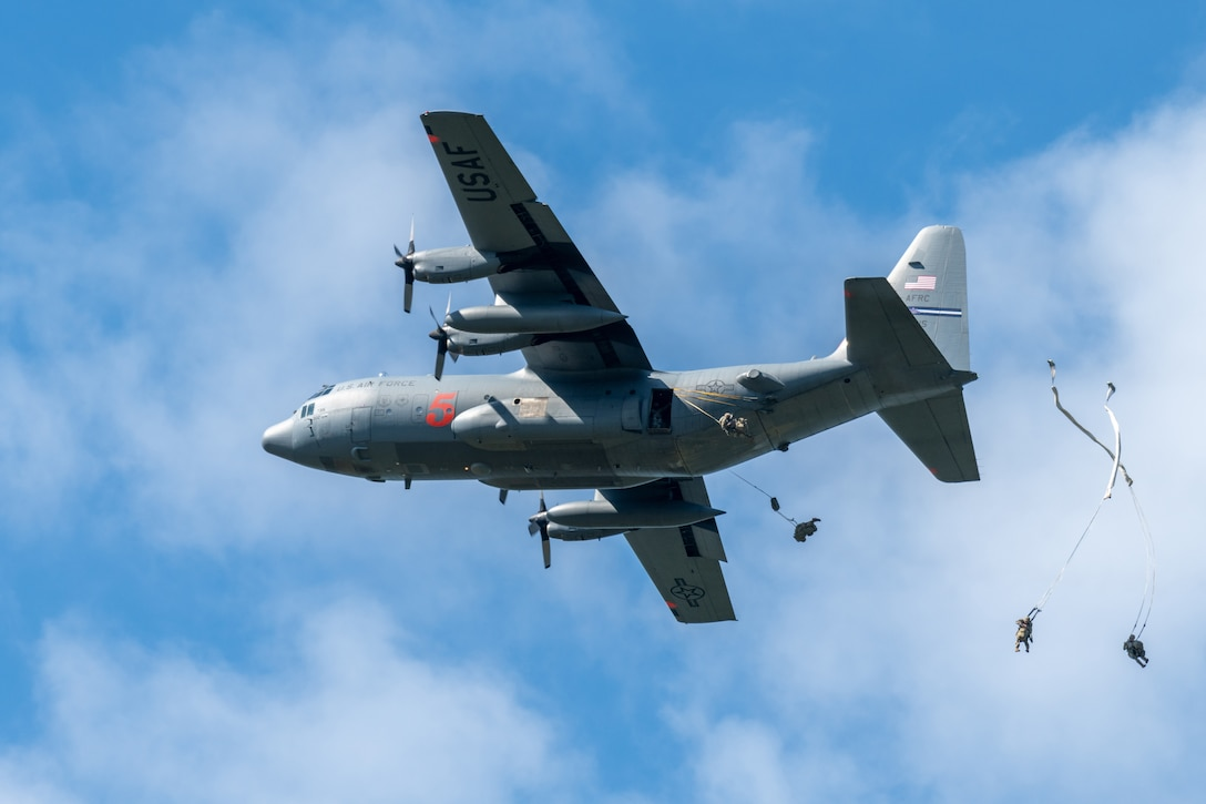 C-130 plane drops Army soldiers out of the back using parachutes.