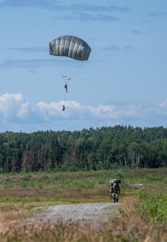 Army soldiers drop to the ground using parachutes.