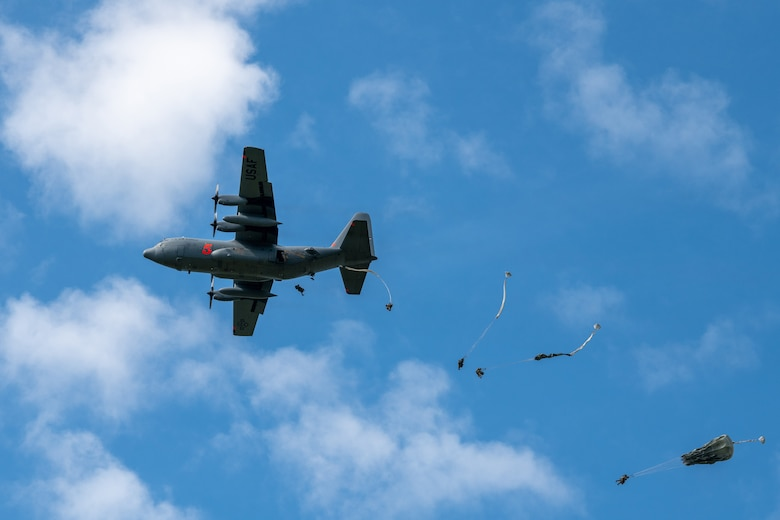 Plane flies through sky, Army soldiers deploy out using parachutes.