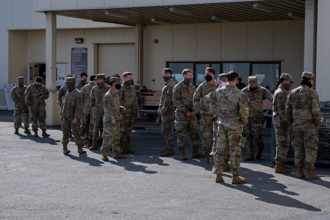 Army soldiers prep for training and receive gear to perform jump training.