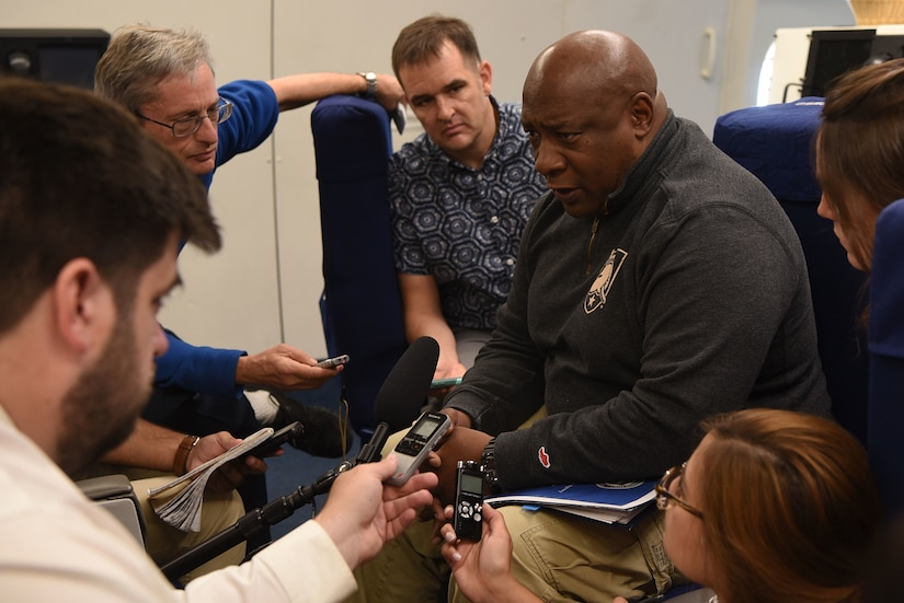 Man sits among five reporters with microphones and notepads.