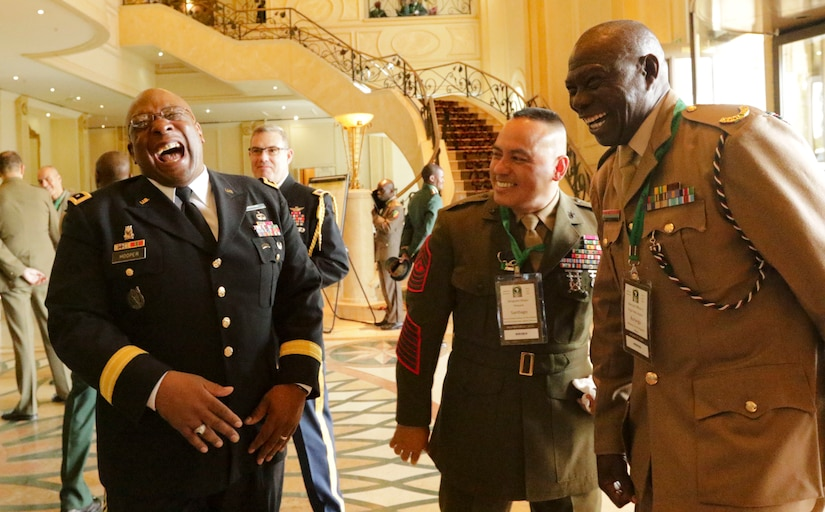 Three men in military uniforms laugh together in a large foyer.