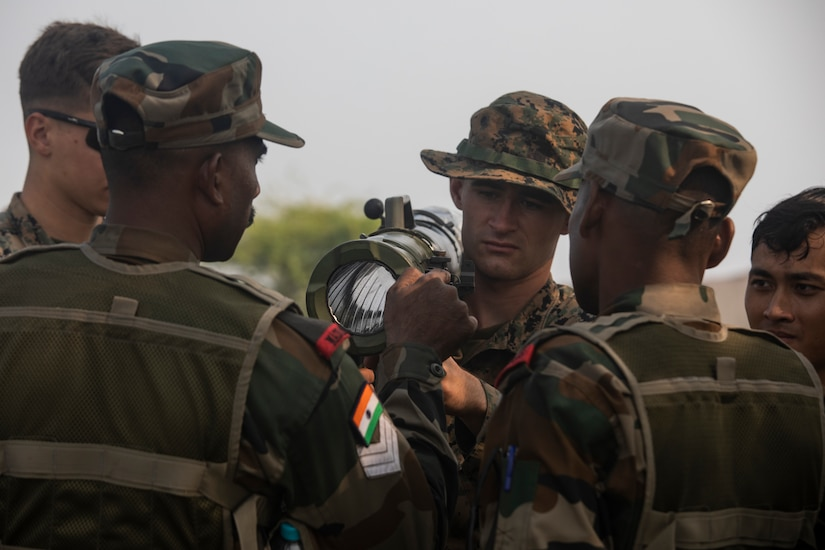 Multiple service members gather around a shoulder-mounted weapon.