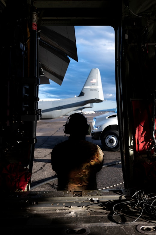 An Airman assigned to the 19th Airlift Wing, waits for a worker at Montrose Regional Airport to finish fueling a C-130J Super Hercules in Montrose, Colorado, July 28, 2020. Support squadrons in addition to the 41st Airlift Squadron trained in Colorado as a part of the 4/12 deployment initiative, which was developed in 2019 between airlift squadrons from Dyess Air Force Base, Texas and Little Rock AFB. The initiative allows for each squadron a full year of dwell time followed by a four-month rotation to their respective area of responsibility. (U.S. Air Force photo by Senior Airman Kristine M. Gruwell)