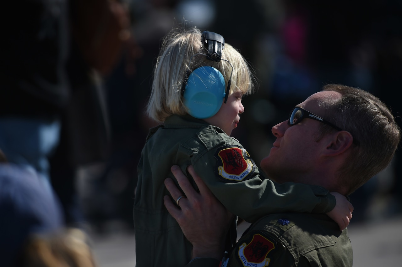 A man wearing a military uniform holds a small boy in the air. The boy is wearing a military uniform similar to that of the man.