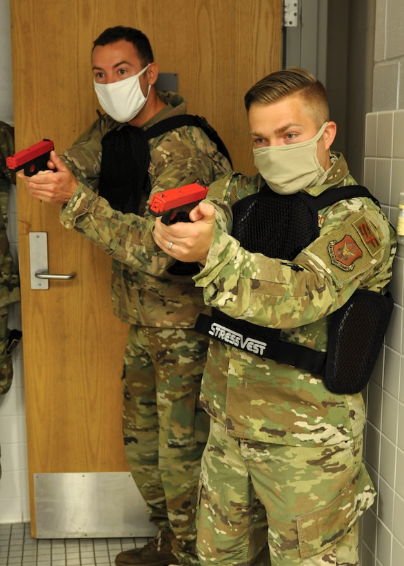 Staff Sgt. Johnathan Rogers, front, and Staff Sgt. Luke Gehring, 445th Security Forces Squadron, engage a target in a locker room during a use of force training on July 12, 2020. The training, designed to closely mirror real-world scenarios, incorporated vests which deliver a minor electric shock to the wearer if another participant makes positive contact with a simulated firearm. (U.S. Air Force photo/1st Lt. Rachel Ingram)