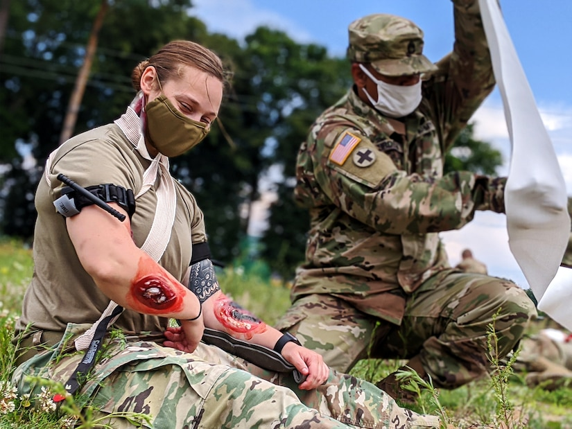 Sfc. Theodore Durden with Task Force Illini, 33rd Infantry Brigade Combat Team, Illinois National Guard applies life saving point of injury care to Sgt. Emily Beyer of Task Force Juvigny at Collective Training Center- Yavoriv, Ukraine,  July 27.