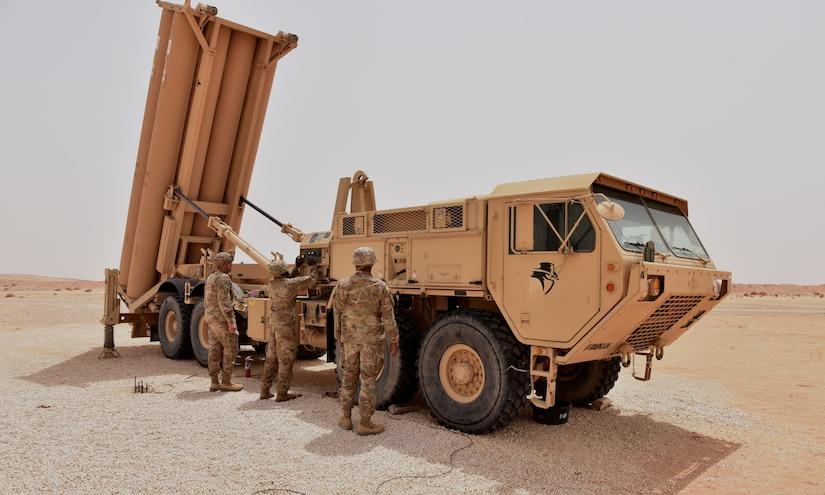 Three service members work on a large military vehicle in the desert.