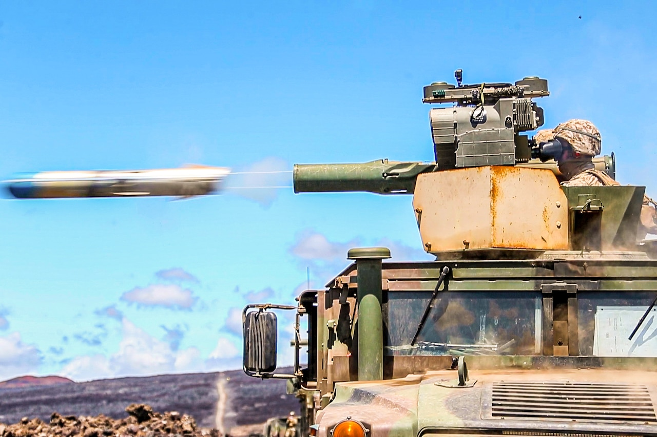 A missile shoots out from the turret of a military vehicle manned by a Marine.