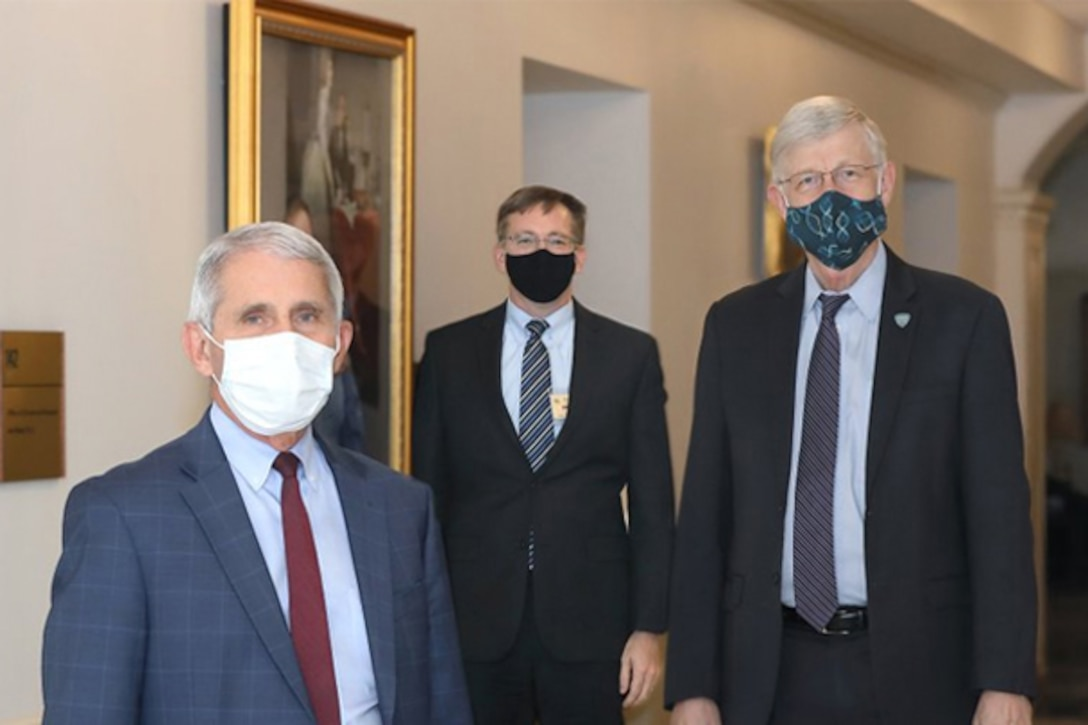 Three civilians wearing face masks stand for a photo.