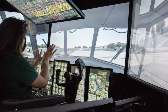 Heather Bernat from Dover Public Library reacts after successfully landing in the C-130 flight simulator