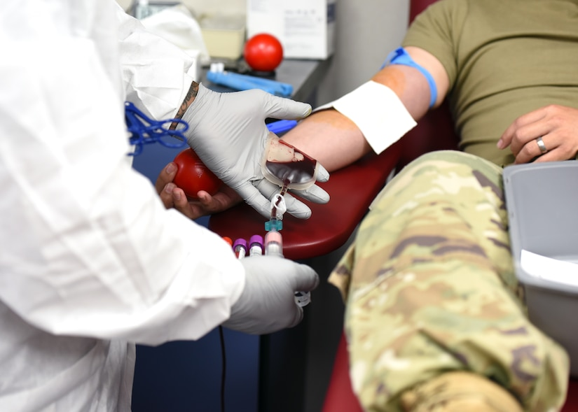 Gloved hands of a technician fill vials with blood from a donor's arm.
