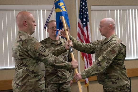 Capt. Rod Toms, right, accepts the 167th Security Forces Squadron guidon, from Col. Bill Annie, 167th Mission Support Group commander, during a change of command ceremony at the 167th Airlift Wing, Aug. 1, 2020. Lt. Col. Tim Rice relinquished command of the squadron to Toms during the ceremony.