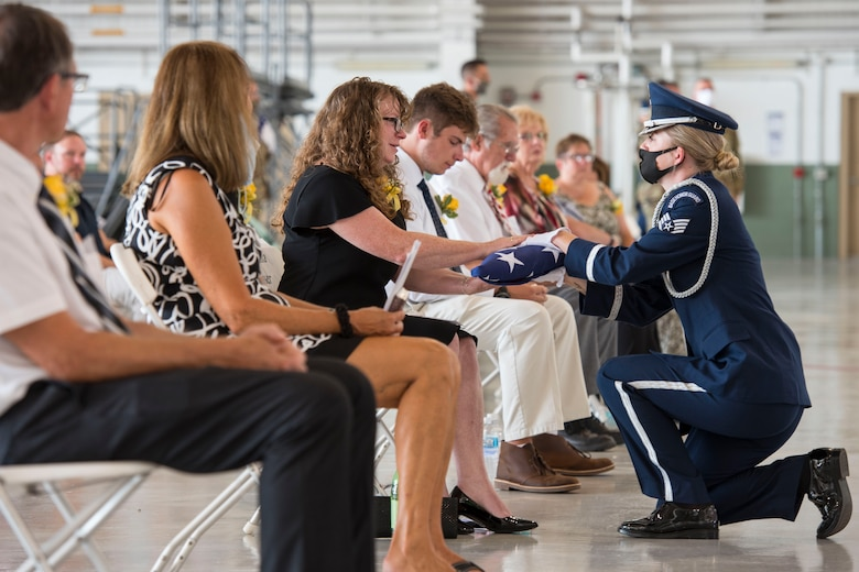 Staff Sgt. Kayla Hoffmaster, 167th Airlift Wing honor guard member, presents an American flag to Mrs. Donna Nasser during the memorial service for Lt. Col. Chris Nasser held at the 167th Airlift Wing, Aug. 2. Nasser wife Donna, and son Colin, were presented with Lt. Col. Nasser's Meritorious Service Medal, West Virginia Legion of Merit and a shadowbox representing his 30 year military career.