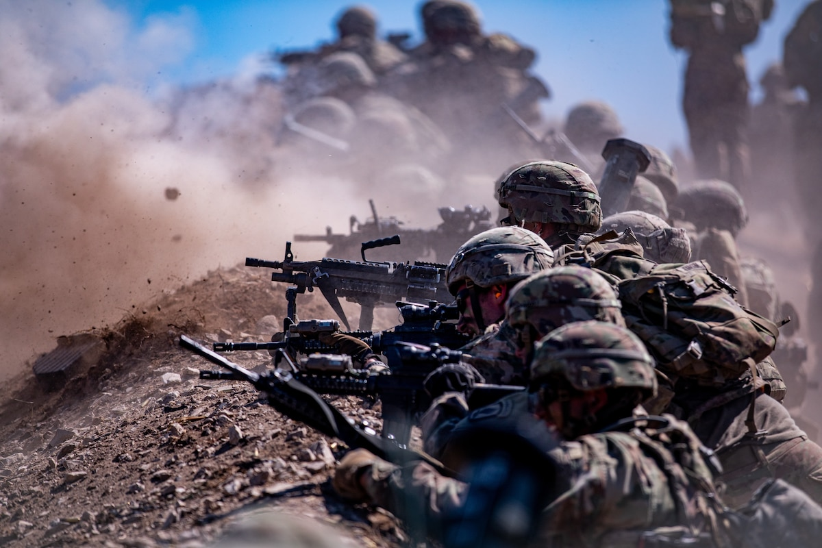 Soldiers lay in a line and aim weapons as dirt clouds rise in the background.