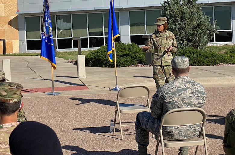 A woman stand outside near two flags speaking to an audience.