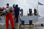 Coast Guard Cutter Legare crew members offload about 3,900 pounds of marijuana.