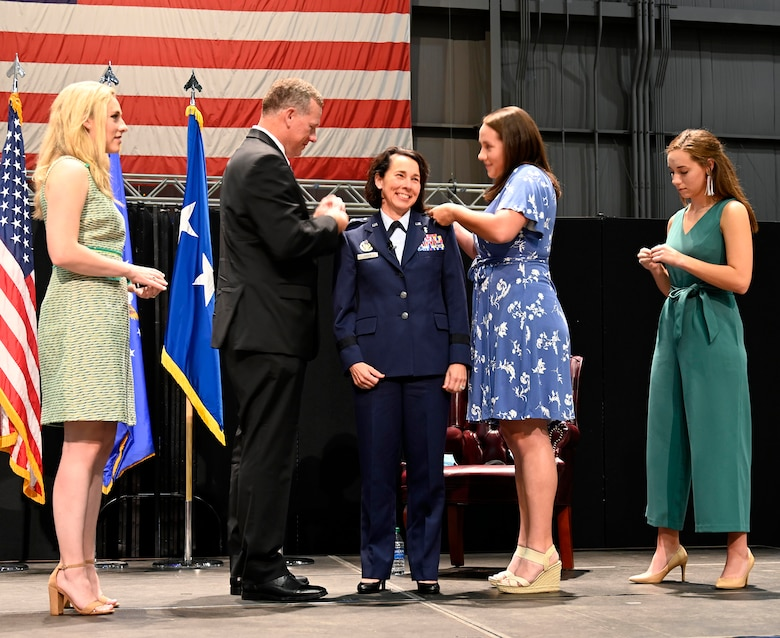 Col. Jeannine Ryder smiles as her family pins the rank of brigadier general on her uniform Aug. 3 at the National Museum of the United States Air Force, Wright-Patterson Air Force Base, Ohio. (photo by Darrius Parker)