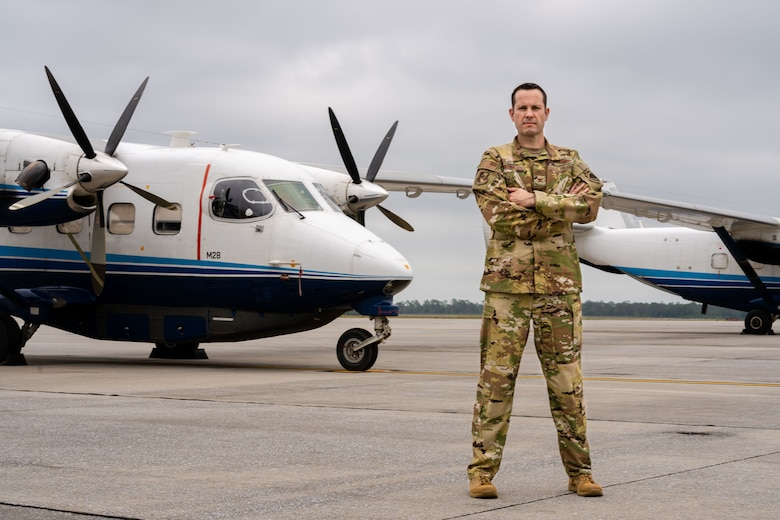 Airman stands in front of aircraft.