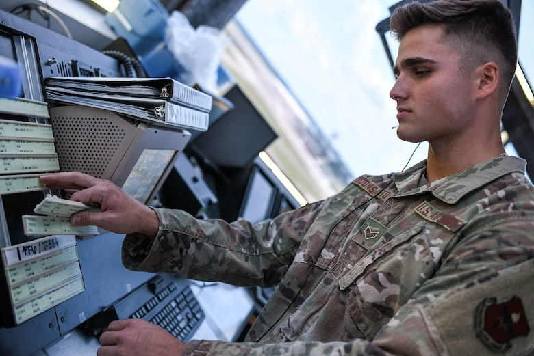 Senior Airman Nico Buonsanto, 14th Operations Support Squadron Air Traffic Controller, moves flight strips while in the new Tower Coordinator position August 4, 2020, on Columbus Air Force Base, Miss. Columbus AFB Air Traffic Control Tower leadership developed and implemented the new Tower Coordinator (CT) position, effective June 1, 2020, splitting the duties and responsibilities of the overtasked Flight Data (FD) position. (U.S. Air Force photo by Senior Airman Keith Holcomb)