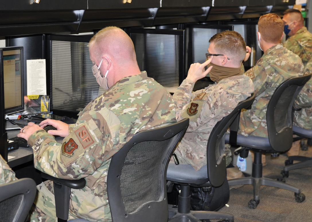 Master Sgt. Kevin Kelly (far left) and Staff Sgt. Mitchiner Underhill and other members of the 445th Security Forces Squadron, work to complete required readiness training in the 445th SFS computer lab, despite new challenges associated with the COVID-19 pandemic. To protect themselves and others, members of the squadron wore masks and sanitized high-touch areas throughout the day, in addition to sanitizing communal work stations, like these, before and after each use. (U.S. Air Force photo by 1st Lt. Rachel Ingram)