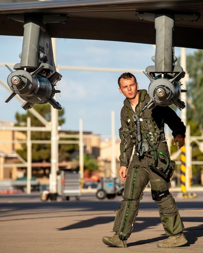 First Lt. Joshua Shook, 63rd Fighter Squadron F-35A Lightning II pilot, inspects an inert GBU-12 laser-guided bomb during a pre-flight inspection July 22, 2020, at Luke Air Force Base, Ariz.