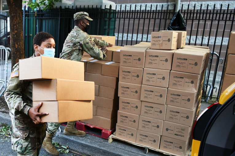 A guardsman wearing a face mask carries boxes of meals to a vehicle for distribution at a food site.