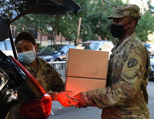 Sgt. Thalia Santos from Yonkers, N.Y., left, and Spc. Kirt Joseph from Brentwood, N.Y., members of the New York Army National Guard, load boxed, packaged food, into a vehicle at a food distribution site in the Bronx, New York Aug. 5, 2020.