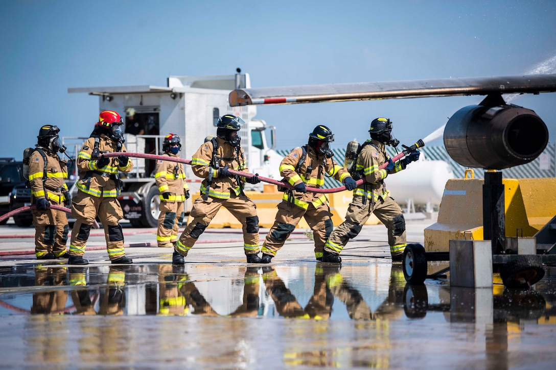 A group of sailors and firefighters battle an aircraft fire.
