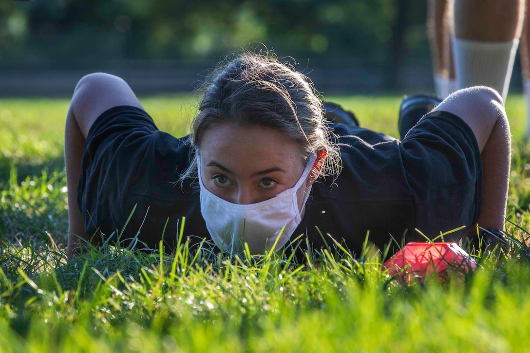 A cadet wearing a face mask does a push up in the grass.