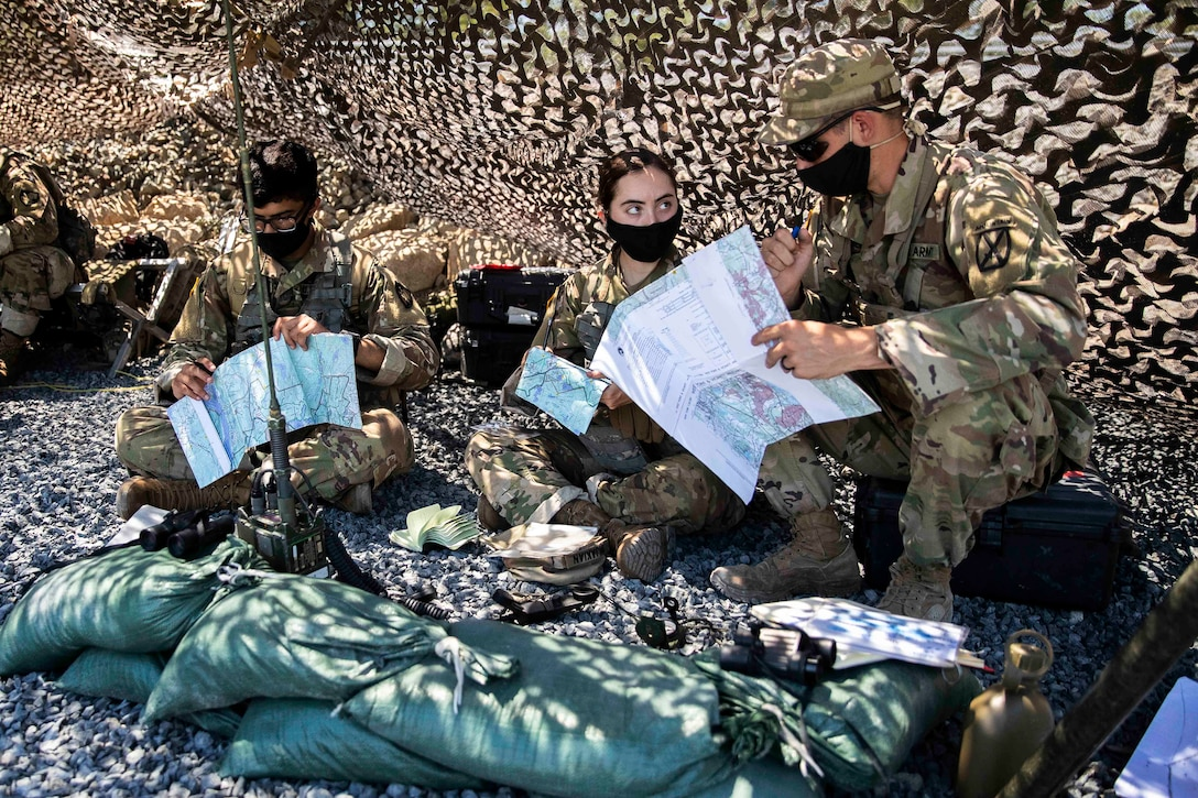 Three Army cadets look at maps underneath a tent.