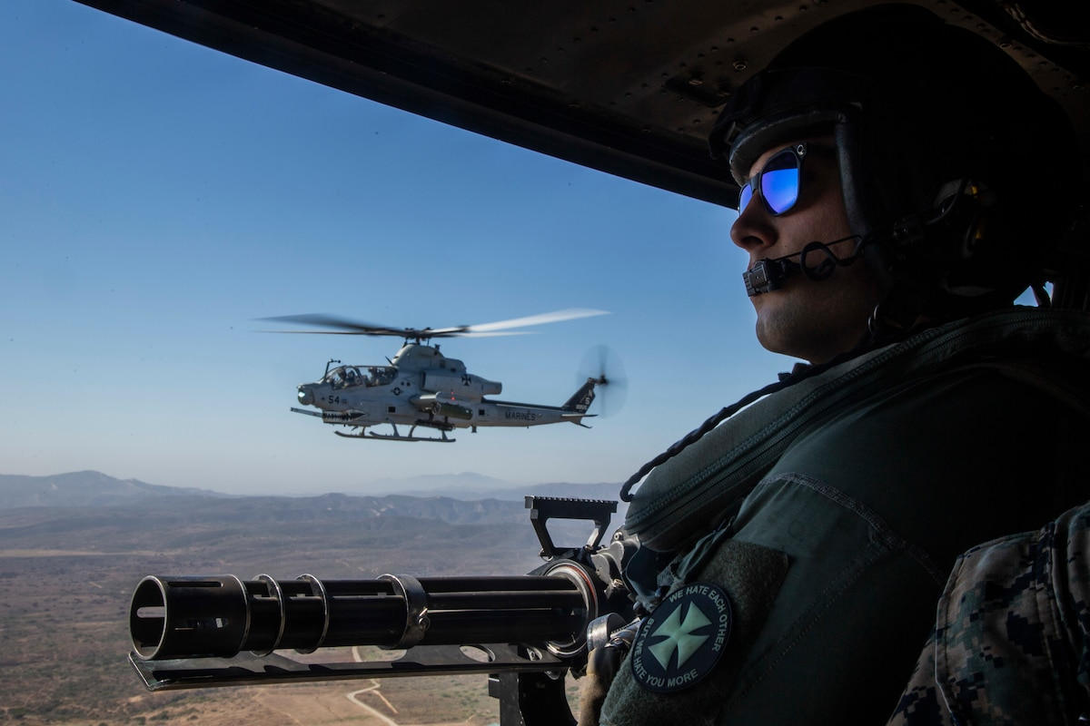 A man flying in a helicopter looks forward.