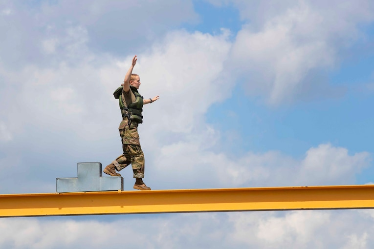 An Army cadet walks along a beam.