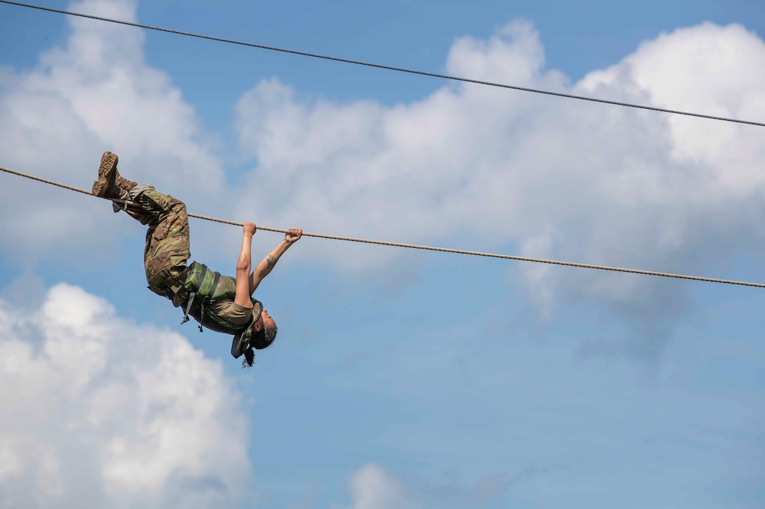 An Army cadet maneuvers across a rope suspended above the ground.