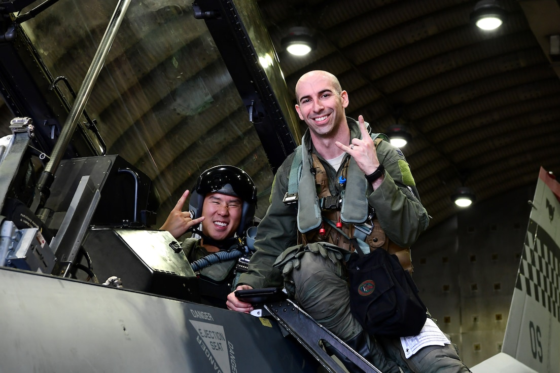 Maj. Chris Ng, 51st Medical Operations Squadron general surgeon, left, and Capt. Louis Bloom, 36th Fighter Squadron F-16 pilot, pose for a photo at Osan Air Base, Republic of Korea, July 28, 2020. Both hailing from Randolph, Massachusetts, the Randolph High School graduates continued their friendship while attending the United States Air Force Academy. Rekindling at Osan Air Base, their familiarization flight plans were initially derailed due to Bloom's motorcycle accident. Ng's medical expertise was instrumental to Bloom's full and speedy recovery during the surgical and rehabilitation process, ultimately resulting in finally flying together. (U.S. Air Force photo by Senior Airman Noah Sudolcan)