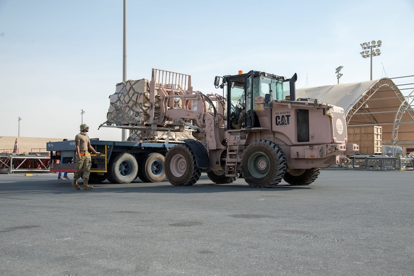 Military personnel use loading equipment to move supplies.