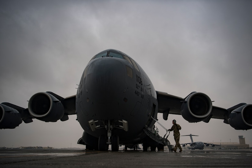A service member approaches the staircase attached to a large military aircraft.