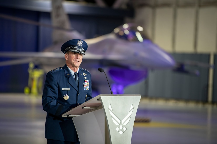 An Air Force general speaks at a lectern in an aircraft hangar with a jet in the background.