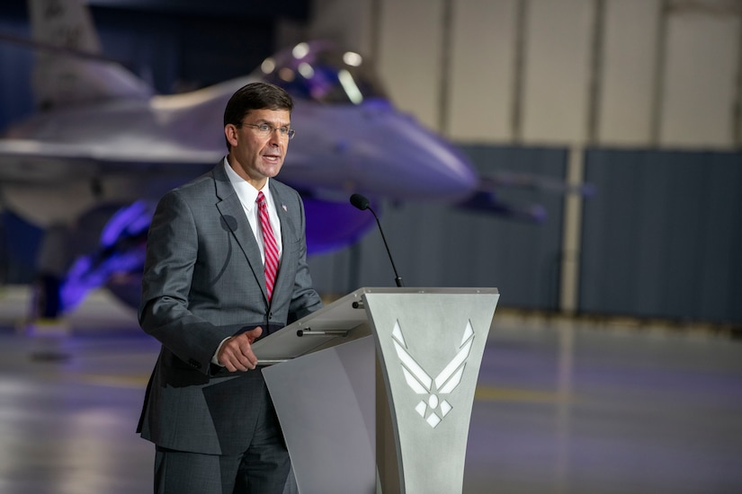 Man speaks at a lectern in an aircraft hangar with a jet in the background.