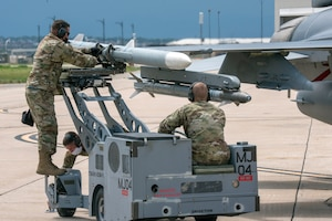 2 Airmen loading a missile on the wing of an F-16