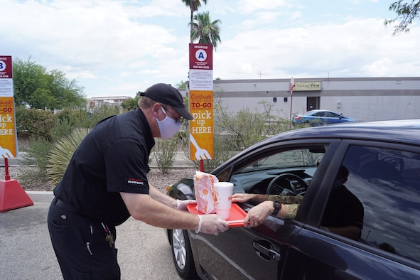 A photo of a man giving food to a drive-thru passenger