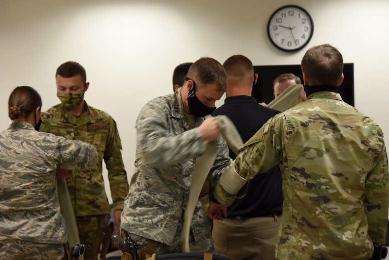 Photo of Airmen practicing applying pressure to a wound