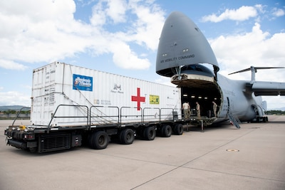 Airmen move a large container from the open cargo bay of a C-5B transport jet to a trailer on the tarmac.