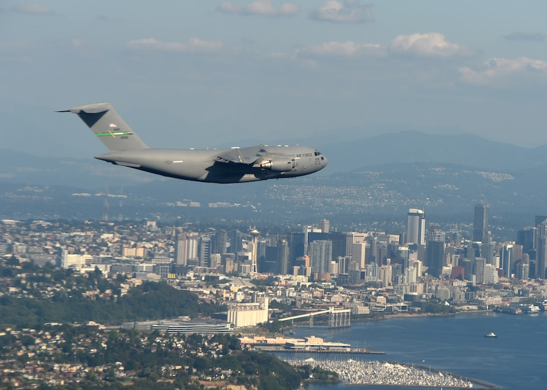A C-17 Globemaster III from Joint Base Lewis-McChord flies over the Seattle skyline after completing a low-level formation training exercise in central Washington, Aug. 5, 2020. Flying in a formation of two or more aircrafts in a combat scenario allows for tactical advantage by establishing mutual support and mass of aircraft over an objective area.  (U.S. Air Force photo by Airman 1st Class Mikayla Heineck)